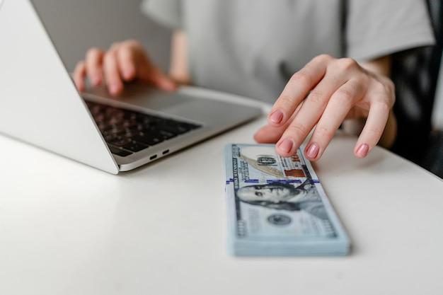 Freiberufliche frau, die laptop-computer verwendet, der geld nahaufnahme verdient