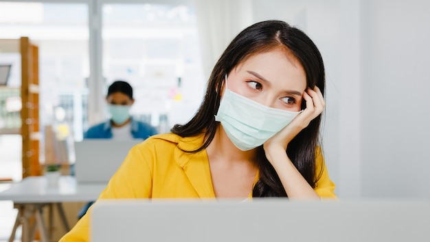 Freiberufliche frauen aus asien tragen eine gesichtsmaske mit harter arbeit des laptops im neuen normalen heimbüro. arbeiten von hausüberlastung, selbstisolation, sozialer distanzierung, quarantäne zur vorbeugung von koronaviren.