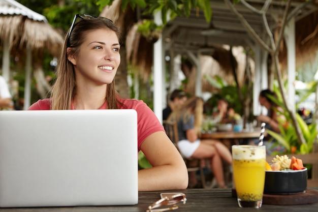 Freiberufliche kaukasierin mit langer frisur, die aus der ferne an einem modernen laptop-pc arbeitet und während des frühstücks im café kostenloses wlan nutzt