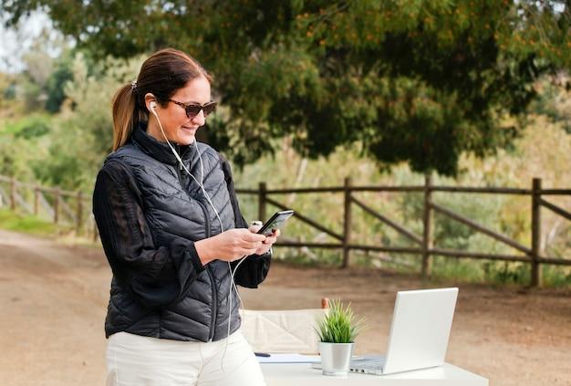 Freiberufliche mädchen tippen am telefon und schauen auf den bildschirm mit einem laptop auf dem bürotisch und mit einer schönen aussicht auf himmel und grün. reisen sie mit einem computer. traumjob online in der natur
