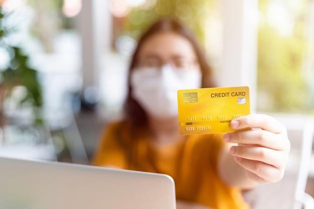 Freiberufliche menschen geschäftsfrau tragen schutzmaske lässig abstrakte unschärfe mit fokus auf show halten eine kreditkarte mit laptop arbeiten