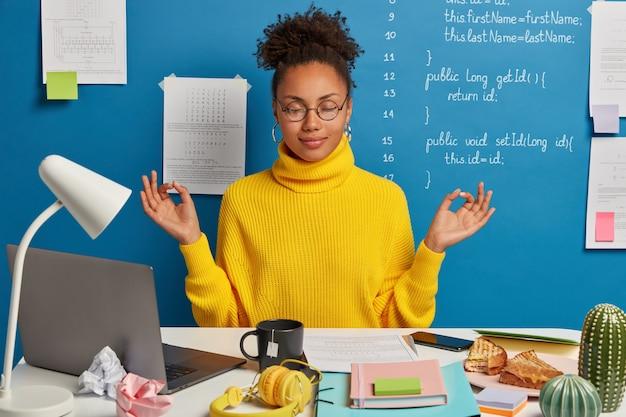 Freiberufliche mitarbeiterin macht yoga am arbeitsplatz, genießt eine ruhige, ruhige atmosphäre, trägt eine runde brille und einen pullover