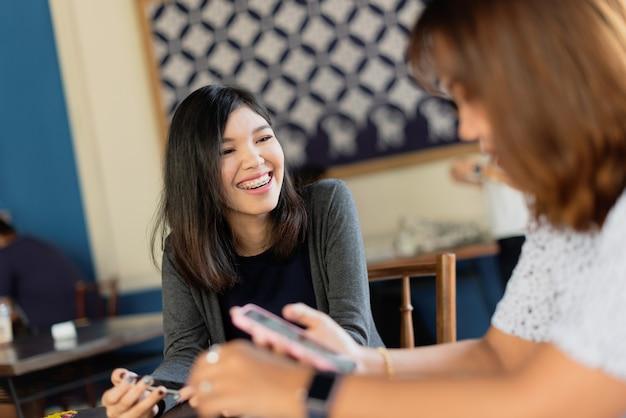 Freiberufliche sitzung der asiatischen mädchen mit kollegen am coffeeshop.