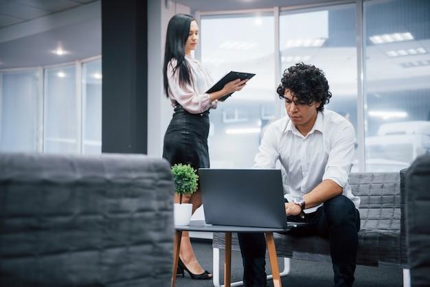 Freiberufliche tätigkeit im büro mit fenstern dahinter. zwei personen sind berufstätig. kerl, der silbernen laptop verwendet. mädchen las dokument