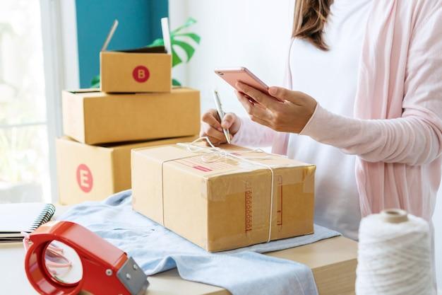 Freiberufliche verkäuferin bereitet paketbox des produkts für die lieferung an den kunden vor