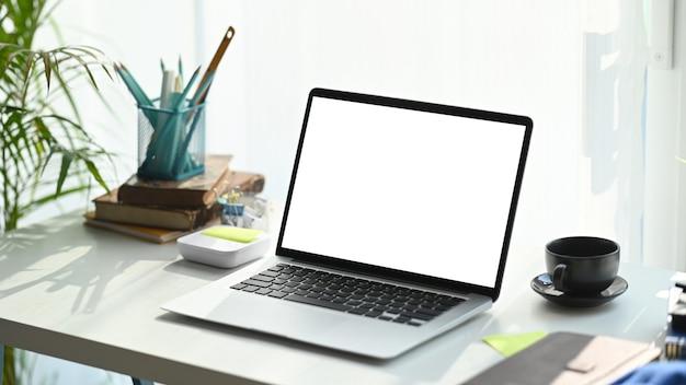 Freiberuflicher arbeitsplatz mit computer-laptop, notebook, kaffeetasse und pflanze auf weißem schreibtisch.