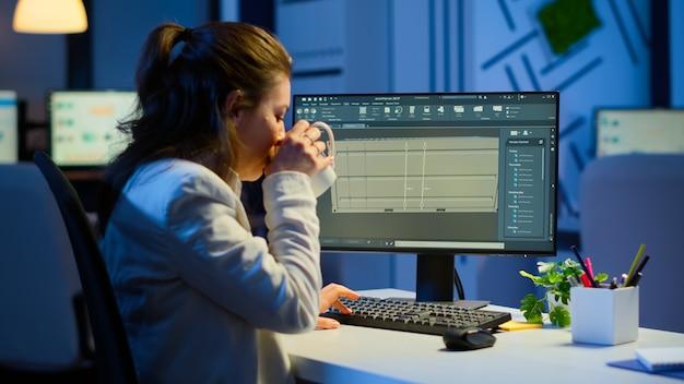 Freiberuflicher architekt, der in 3d-software arbeitet, um das containerdesign zu erarbeiten, das um mitternacht am schreibtisch im geschäftsbüro sitzt. konzentrierter ingenieur, der prototypen erstellt und untersucht und maßstabsgetreue modelle analysiert.