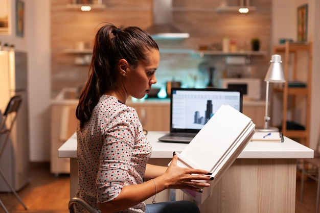 Freiberuflicher architekt, der nachts im home office arbeitet und ein gebäudemodell für einen kunden hält. ingenieurkünstler, der im büro erstellt und arbeitet, das maßstabsgebäudemodell, entschlossenheit, karriere hält