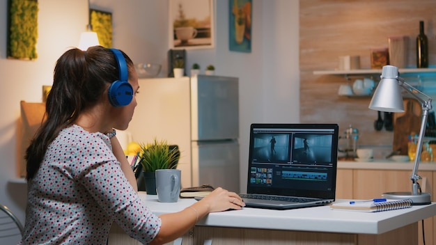 Freiberuflicher content-ersteller, der von zu hause aus überstunden macht, um die frist einzuhalten. frau videofilmerin, die audiofilmmontage auf professionellem laptop bearbeitet, der um mitternacht auf schreibtisch in moderner küche sitzt