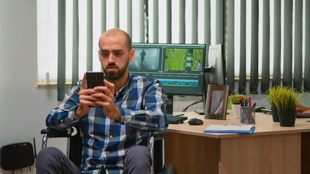 Freiberuflicher fotodesigner mit behinderung im rollstuhl, der auf dem smartphone eine pause von der bearbeitung von videoprojekten macht und inhalte in einem modernen firmenbüro erstellt. blogger, der vom fotostudio arbeitet.