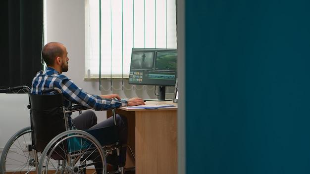 Freiberuflicher fotodesigner mit behinderung in der rollstuhlbearbeitung postproduktion eines videoprojekts, das inhalte in einem modernen firmenbüro erstellt. videograf, der vom fotostudio arbeitet.