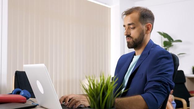 Freiberuflicher geschäftsmann, der am laptop im haus arbeitet, und seine frau ist im hintergrund