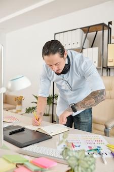 Freiberuflicher grafikdesigner, der die uhrzeit überprüft, ist die armbanduhr, wenn er notizen im planer macht