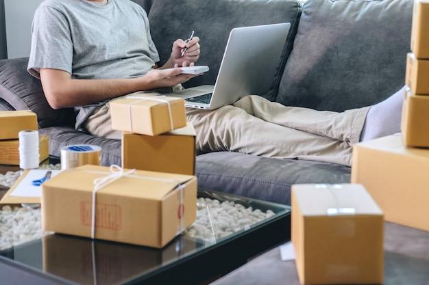 Freiberuflicher mann des jungen unternehmers kmu, der mit anmerkungsverpackungsartkasten-anlieferungsonline-markt auf bestellung arbeitet