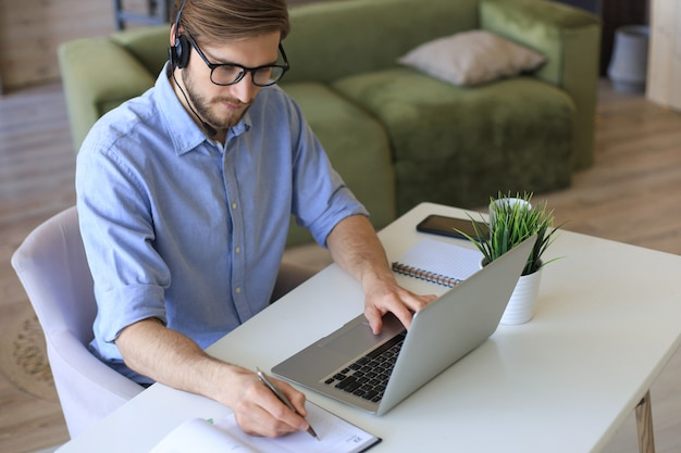 Freiberuflicher operator, der mit headsets spricht und kunden aus dem home-office berät.