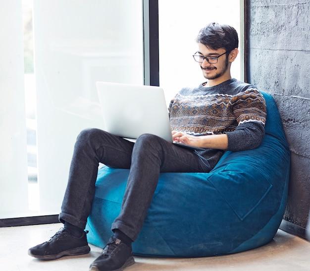 Freier büroraum, männlicher angestellter, der nahe bei einem fenster mit seinem laptop sitzt
