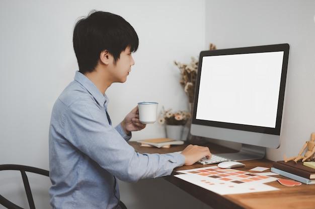 Freier freiberufler des jungen kreativen grafikdesigners, der mit computermodell des weißen bildschirms zu hause arbeitet.