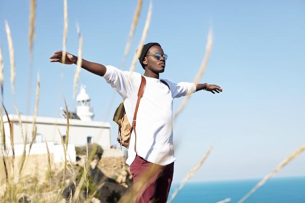 Freier glücklicher stilvoller männlicher tourist, der entspanntes und sorgloses aussehen hat, während er auf einer klippe steht, arme wie ein vogel ausbreitet und an einem sonnigen tag während seiner auslandsreise einen warmen wind spürt. sommerkonzept