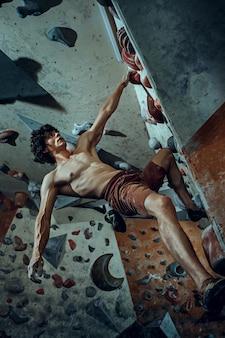 Freier kletterer junger mann, der drinnen künstlichen felsbrocken klettert. kletterkonzept und extreme aktivität. der junge fitte mann am fels