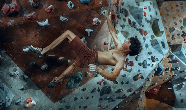 Freier kletterer junger mann, der künstlichen felsbrocken drinnen klettert.