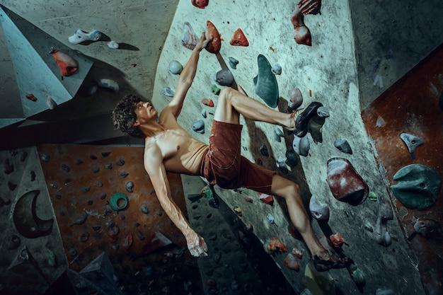 Freier kletterer junger mann klettert künstlichen felsbrocken drinnen