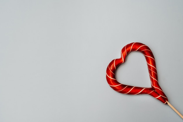 Freier platz für text für den feiertag des valentinsgrußes auf einem blauen hintergrund horizontal. seitenansicht eines süßen karamellherzens.