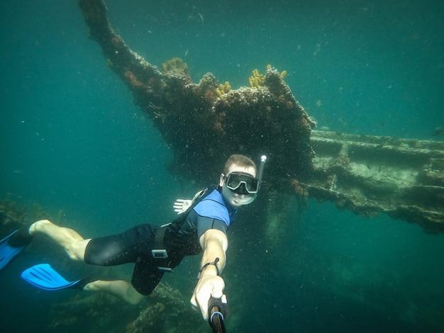 Freier taucher, der selfie mit versunkenem schiff auf hintergrund nimmt.