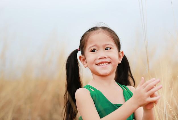 Freies glückliches kindermädchen in getrockneter rasenfläche mit dem lächeln.