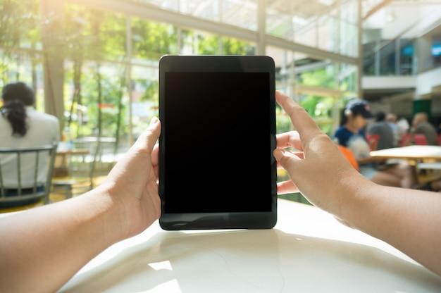 Freigegebene schuss blick auf frau hände halten tablette mit leeren kopie raum bildschirm für ihre sms-nachricht oder informationen inhalt, weibliche lesung text nachricht auf notizblock während der städtischen einstellung