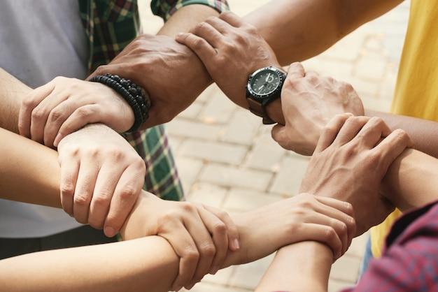 Freigestellte freunde, die handgelenke eines jeden in kette halten, um zu unterstützen und zusammenzuarbeiten