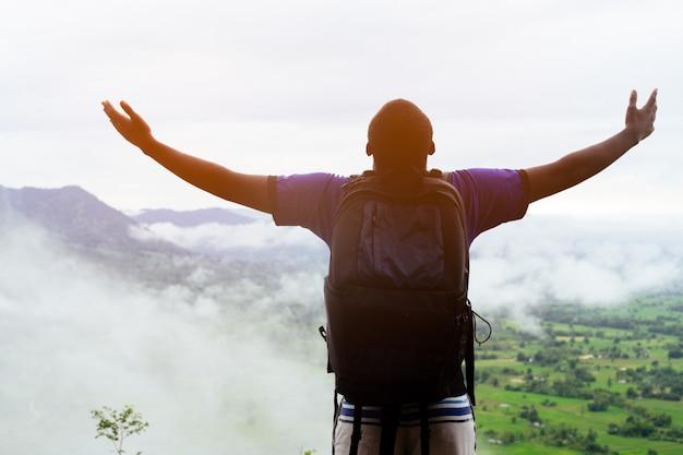 Freiheit afrikanische kletterer stehen oben auf dem mit nebel bedeckten hügel.