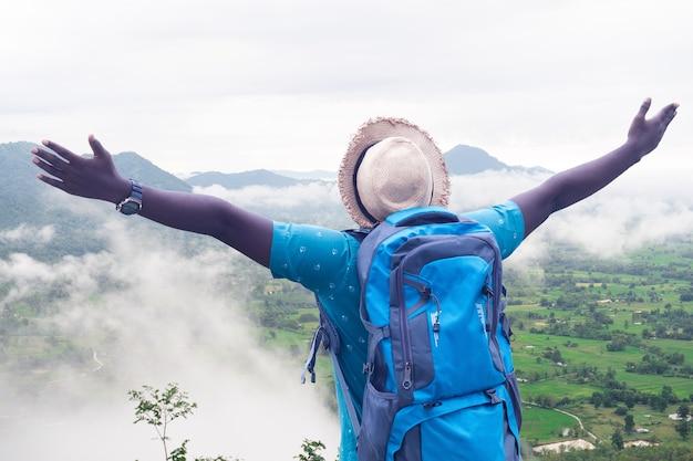 Freiheit afrikanischer mann reisender und wanderer mit rucksack auf der spitze des hügels mit nebel bedeckt
