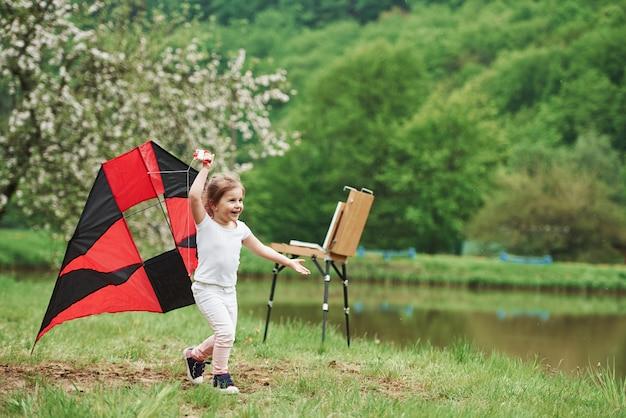 Freiheit fühlen. positives weibliches kind, das mit rotem und schwarzem drachen in den händen draußen läuft