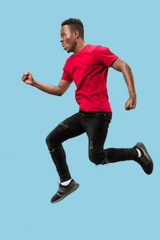Freiheit in bewegung und vorwärtsbewegung. der glückliche überraschte junge afrikanische mann, der vor blauem studiohintergrund springt. runnin mann in bewegung oder bewegung. menschliche emotionen und mimik