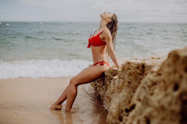 Freiheit junge frau im roten bikini, der auf der klippe nahe meer allein sitzt. sommerberufung