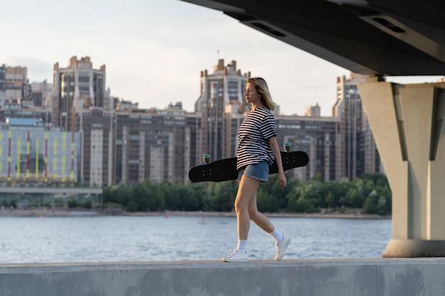 Freiheit lifestyle frau mittleren alters spaziergang in der nähe des flusses halten longboard über großstadtansicht bei sonnenuntergang