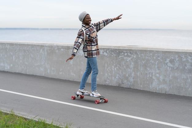 Freiheit und urbaner lebensstil junges mädchen, das auf longboard auf der stadtstraße oder auf dem deck in der nähe von meer skatet