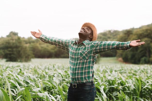 Freiheits-afrikanischer landwirtmannstand am grünen bauernhof mit glücklichem und lächeln.