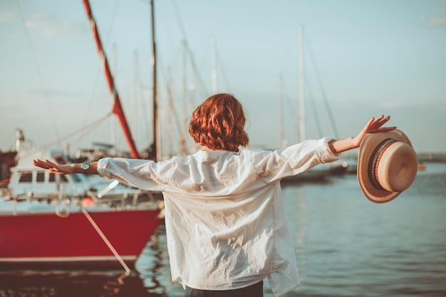 Freiheitsfrau am meer auf dem hintergrund des yachtclubs. entspannungskonzept