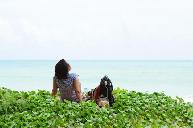 Freiheitsmädchentouristen sitzen auf dem strand.