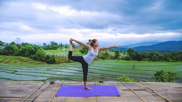 Freiheitsreisende frau entspannen sich im urlaub. spielen sie, wenn yoga steht, landschaften natürlich auf den bergen und feldreis.