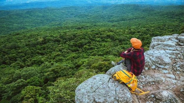 Freiheitsreisende frau genießt einen blick auf die bergnatur auf den klippen vor einer wunderschönen landschaft während der sommerreise, die sich im freien entspannt. reiserucksack