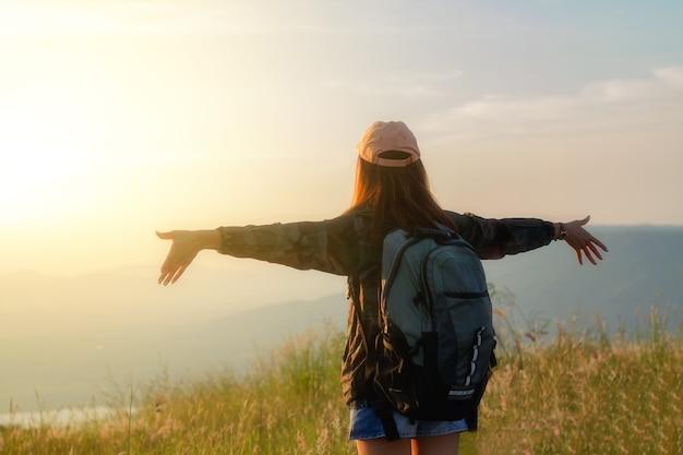 Freiheitsreisenderfrau, die mit den angehobenen armen steht und eine schöne natur genießt und jung zujubelt