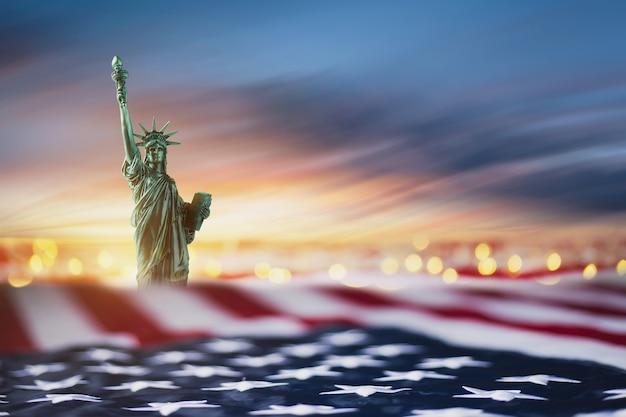 Freiheitsstatue mit usa flagge und bokeh auf sonnenaufgang himmel wolken bewegungsunschärfe. kopierplatz zur verwendung. 4. juli des unabhängigkeitstags. tag der arbeit