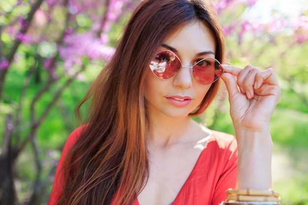 Freiluftfrühlingsnahaufnahmeporträt der brünetten frau, die blumen im sonnigen blühenden garten genießt.