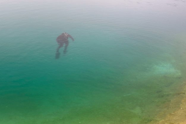 Freitaucher, der oben in das blaue wasser schwimmt