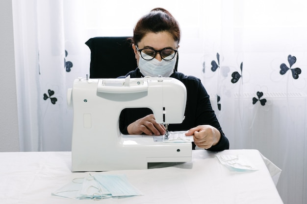 Freiwillige ältere frauen nähen masken, um das virus zu bekämpfen. auf einer weißen nähmaschine nähen. der gemeinschaft helfen. coronavirus pandemie.