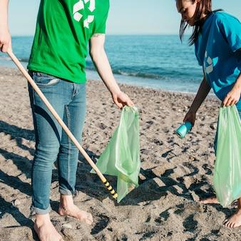 Freiwillige, die abfall am strand mit taschen sammeln
