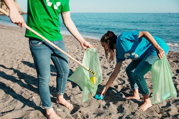 Freiwillige, die abfall am strand sammeln
