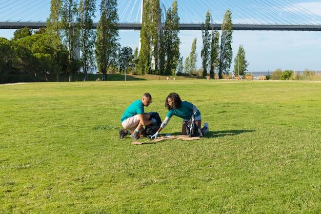 Freiwillige, die abfall vom gras aufheben